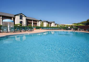 Outdoor pool with umbrellas and beach chairs at Lake Geneva Resort