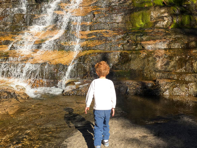 Jessica's son walking toward a small cascading waterfall