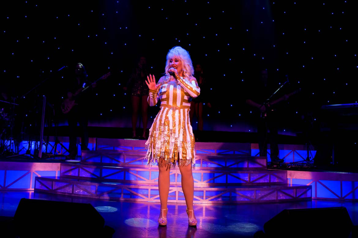 A Dolly Parton impersonator performs onstage with a band in the background at Legends in Concert – Myrtle Beach