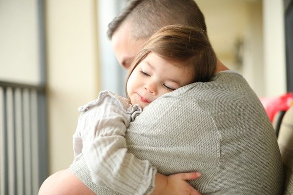 Little girl asleep on her father's shoulder as they sit on a screened-in patio.