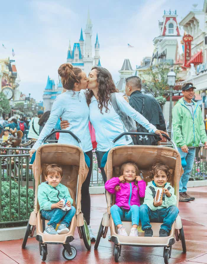 Raff and her wife with their three kids in strollers in front of them with the castle at Magic Kingdom Theme Park in Walt Disney World Resort in the background.