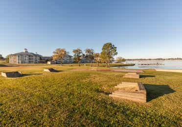 Outdoor shuffleboard court and two horseshoe games with a picnic table at Piney Shores Resort in Conroe, Texas