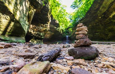 Pile of rocks stacked in front of a waterfall at Starved Rock State Park.