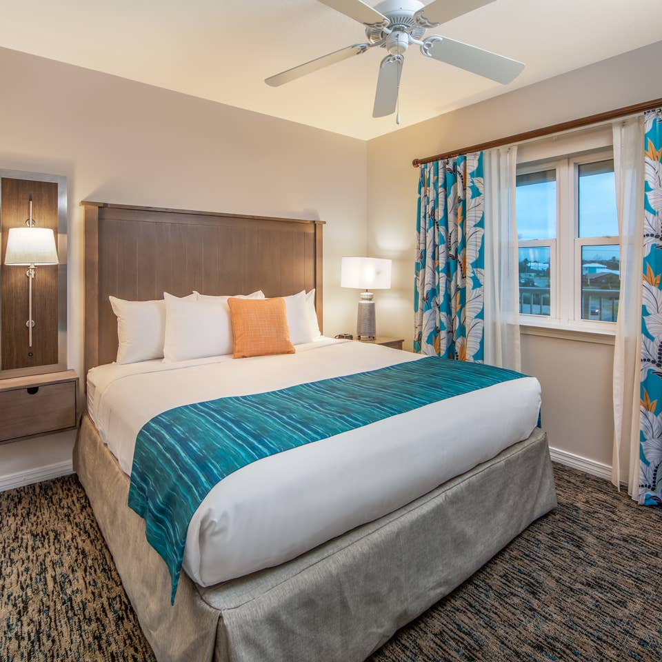 Bedroom with large window with view of ocean and ceiling fan in a two-bedroom villa at Panama City Beach Resort