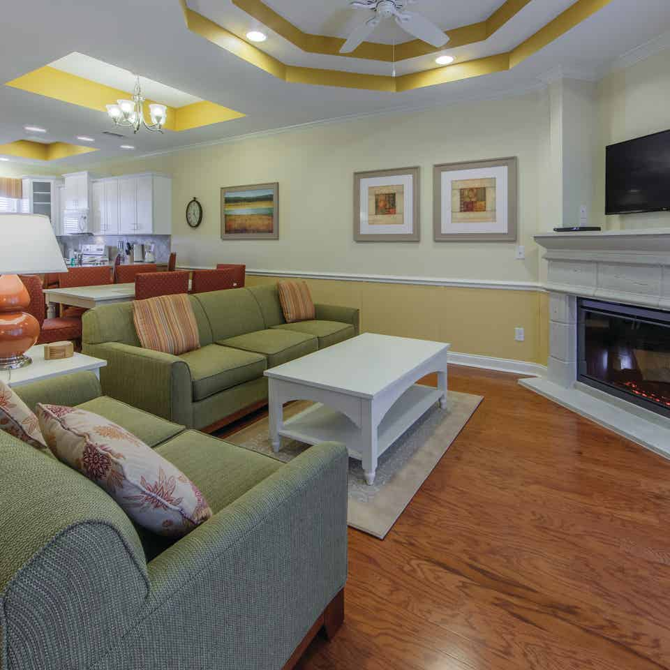 Living room with two couches, fireplace, and flat screen TV in a presidential villa at Fox River Resort in Sheridan, Illinois