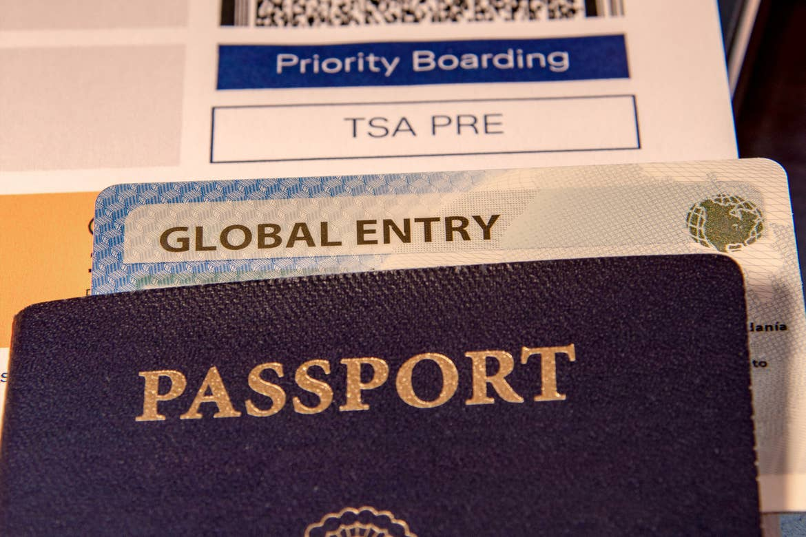 A passport cover placed on top of a ticket with 'global entry' notation and a boarding pass that reads, 'TSA PRE.'