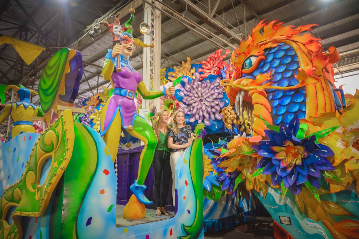 Two caucasian women stand on a retired and vibrant Mardi Gras parade float decorated with dragons and a jester in a warehouse.