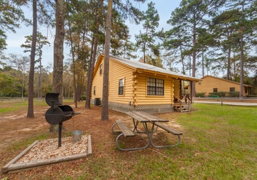 Cabin with BBQ and picnic tables at the Lake O' the Wood Resort in Flint Texas.