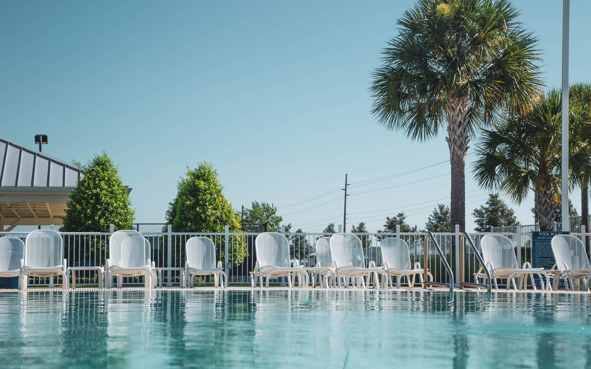 Pool chairs lined up at edge of outdoor pool at Orlando Breeze Resort in Florida.