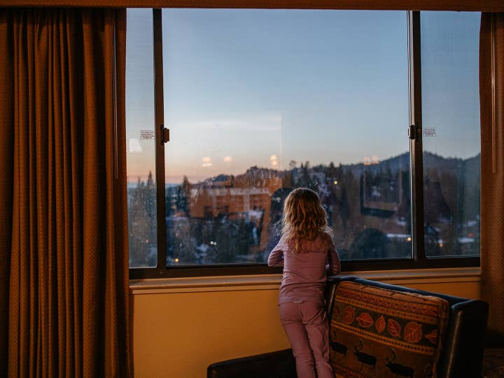 Small child looking out window to view Sierra Nevada Mountains at Tahoe Ridge Resort in Stateline, Nevada.