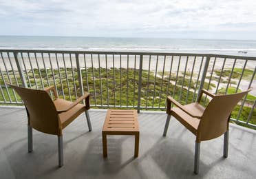 Furnished balcony with two chairs overlooking the beach in a two-bedroom villa at Galveston Beach Resort