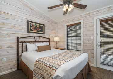Bedroom with queen bed and ceiling fan in a two bedroom cabin at Piney Shores Resort in Conroe, Texas