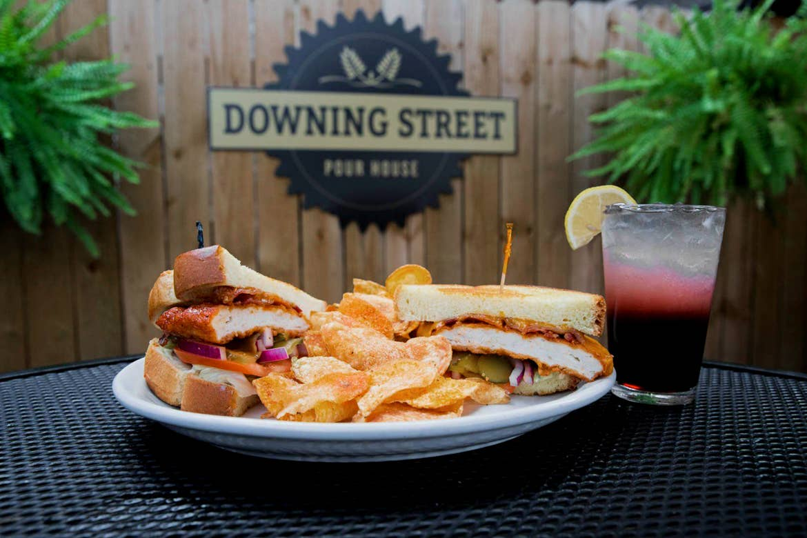 A sandwich split in half, with kettle cooked potato chips are placed on a white plate near a sangria and a picket fence with 'Downing street Pour House' written on it.