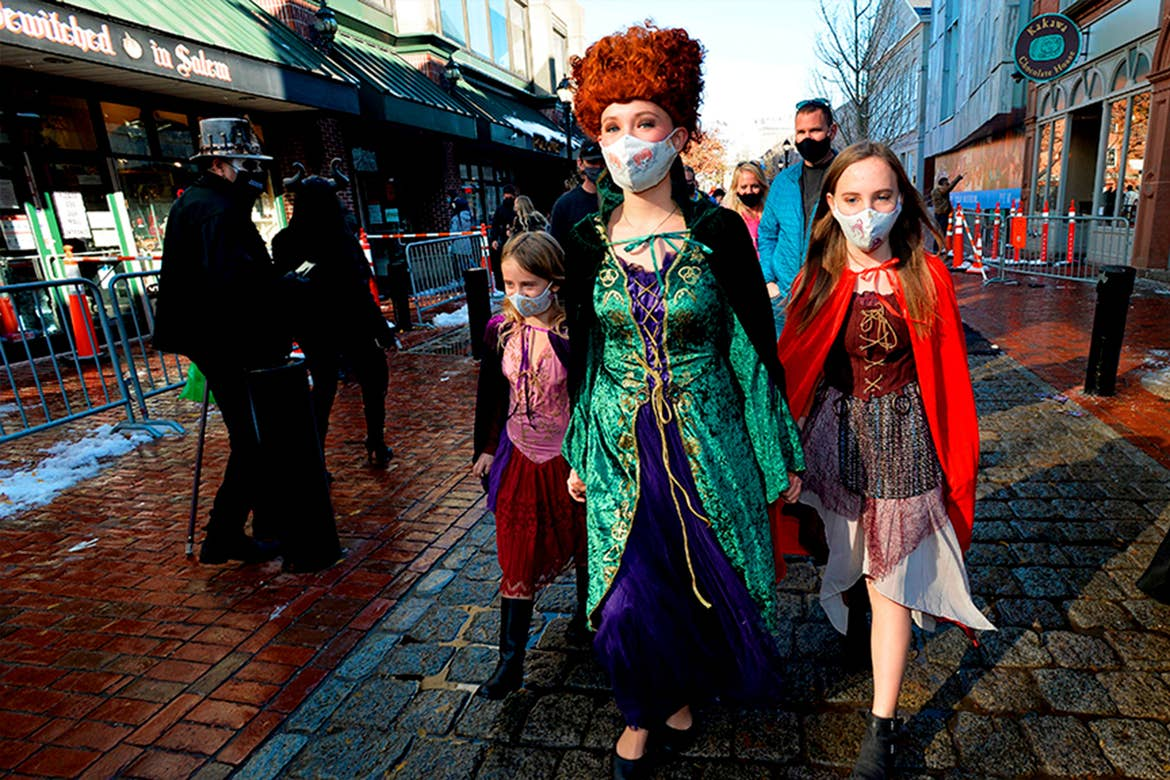 A woman (middle) and two girls (left and right) walk down a brick-paved road wearing safety masks and witch costumes.