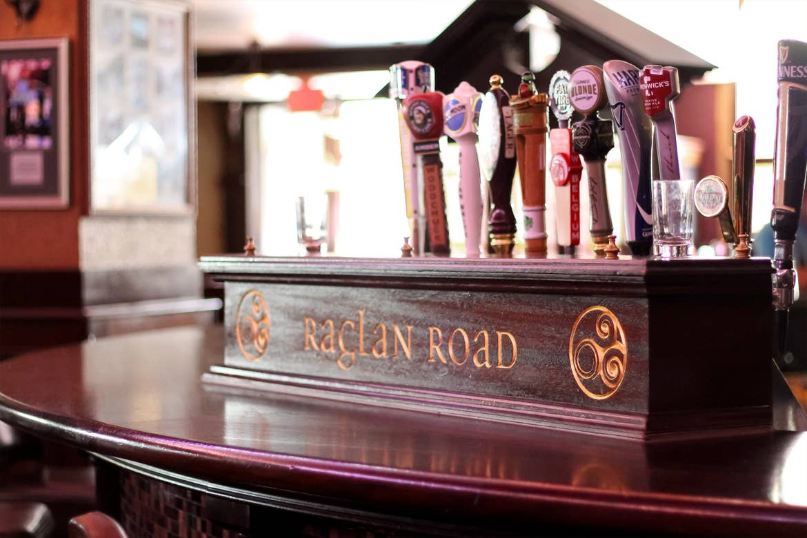 A wooden bar tap cover with 'Raglan Road' engraved on it.