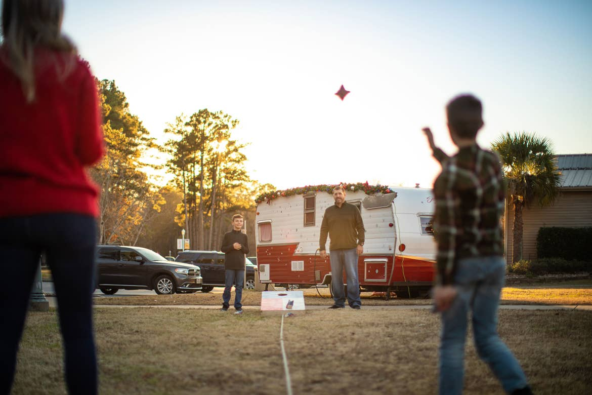 Author, Amanda Nall (left), plays cornhole with her family as the sun sets and they are surrounded with holiday-themed decorations.