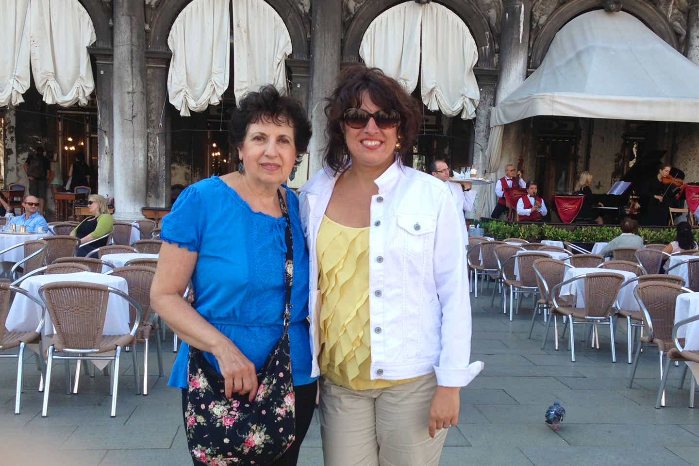 Author, Jennifer Probst (right), wears a white denim jacket and yellow blouse stands next to her mother (left) wearing a blue blouse in front of a restaurant in Venice, Italy.