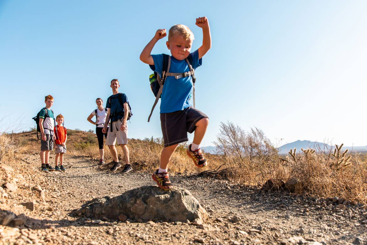 The Averett Family watches as their youngest member bounds over rocks on the trail at Papago Park.