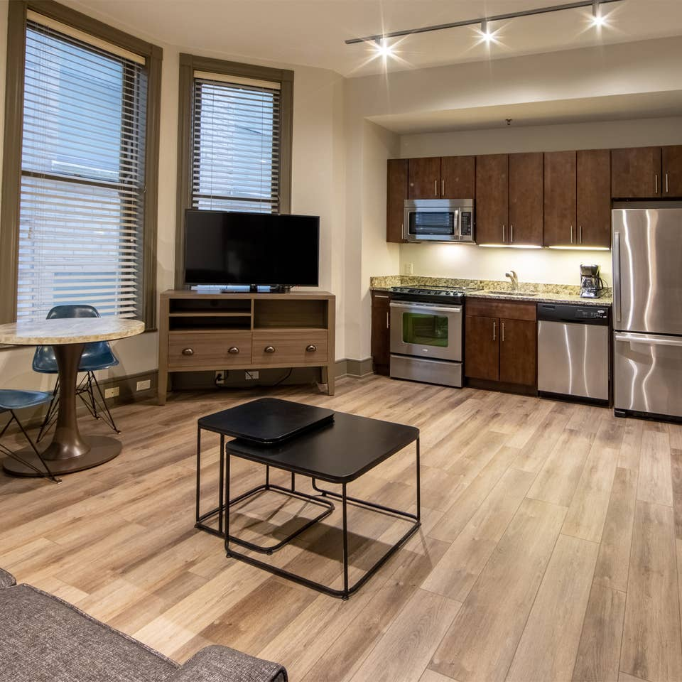 One bedroom villa living area with couch, three windows, TV and full kitchen at New Orleans Resort in Louisiana.