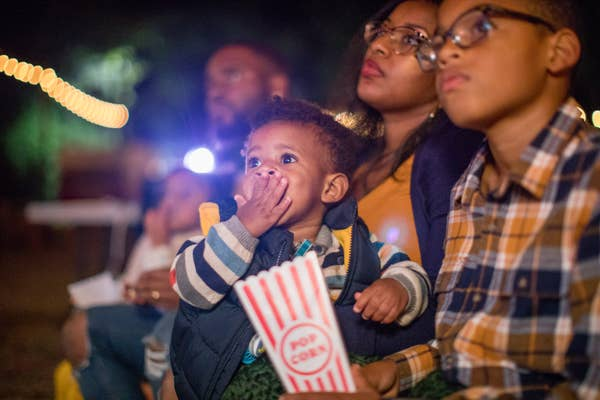 Toddler eating popcorn while watching a movie outside with his family