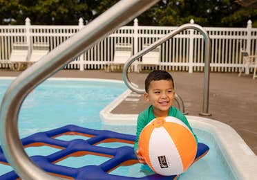 Young child playing with beach ball in outdoor pool at Holiday Hills Resort in Branson, Missouri.