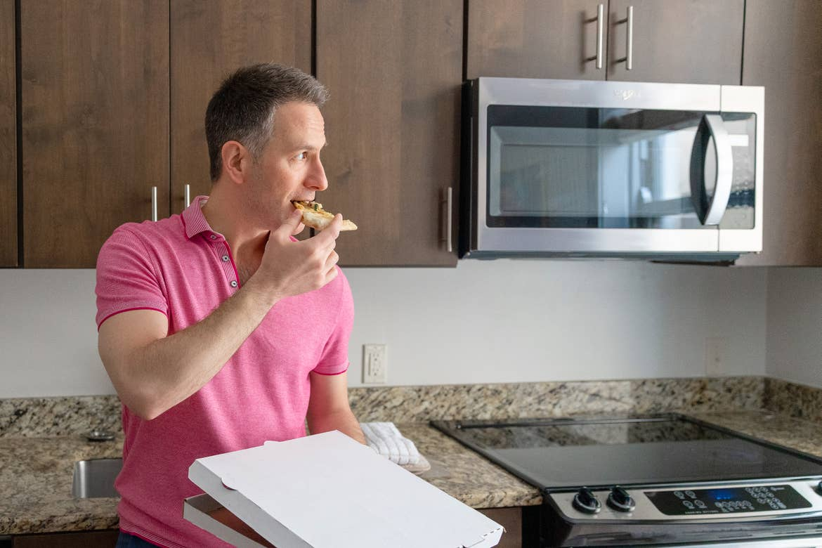 A man (left) wears a pink polo shirt while eating a pizza slice in his right hand and holding a white pizza box in his left hand as he leans on a kitchen countertop.