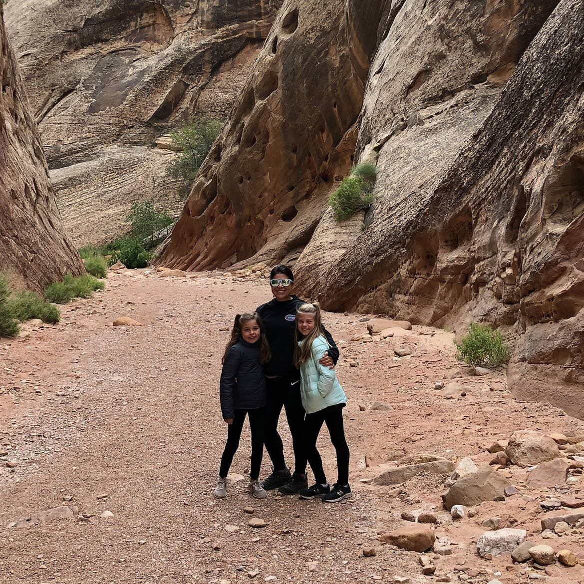 Chris (middle) stands with Kyndall (right) and Kyler (left) in front of rock formations at Capital Gorge.