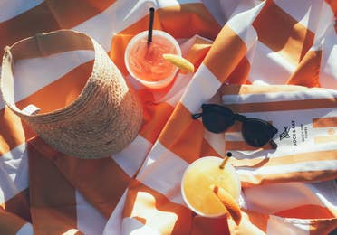 Fruity beverages, sunglasses, and a sun visor on an orange towel in West Village at Orange Lake Resort near Orlando, Florida