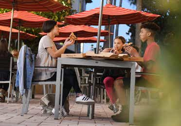 A group of people sitting outside of Paisan Pizzeria at Orange Lake Resort near Orlando, Florida.