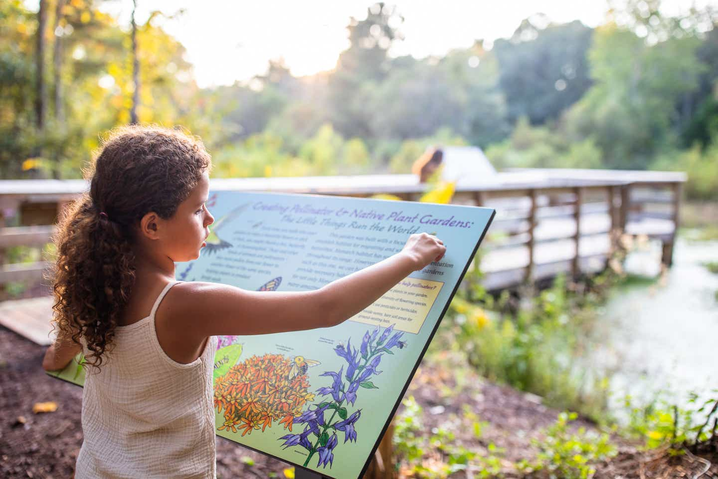 Author, Brenda Rivera Sterns' daughter reads an informational sign at Myrtle Beach State Park, South Carolina.