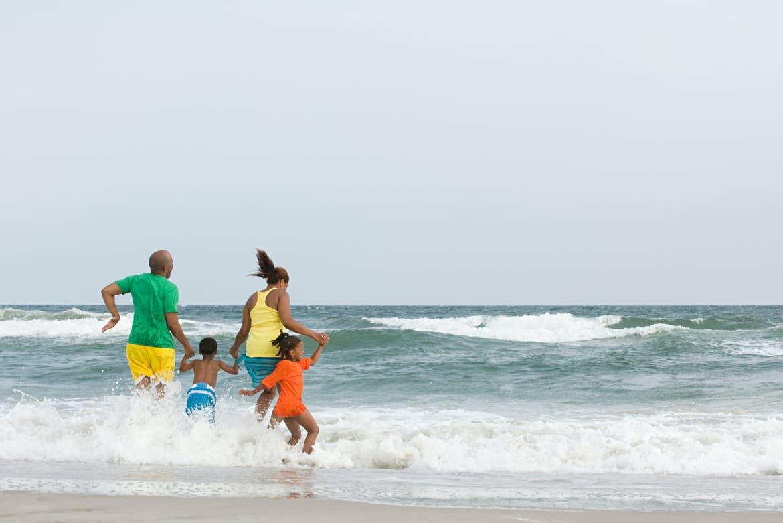 Family jumping in ocean waves