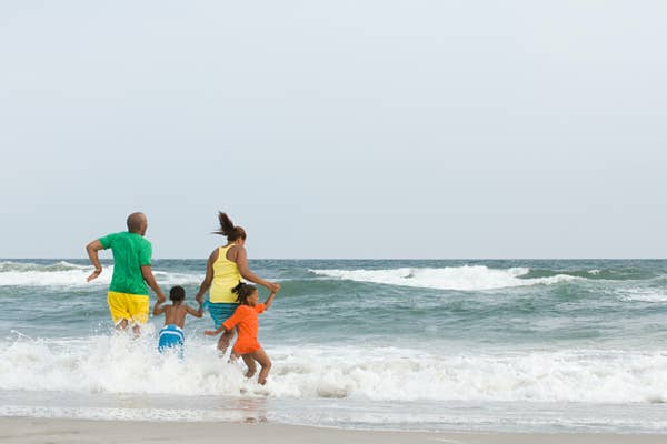 Family running into the waves at the beach.