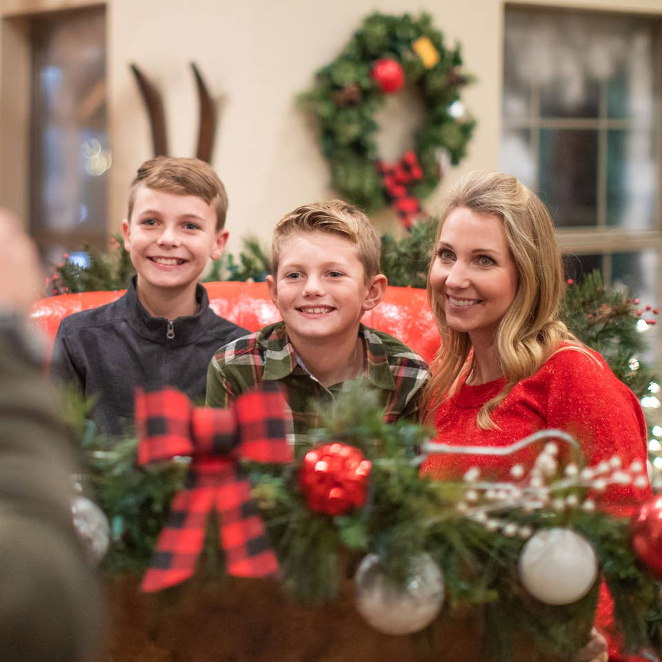 Author, Amanda Nall (right), pose on Santa's sleigh with her sons for a photograph surrounded by holiday decor.