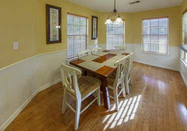 Dining table with six chairs in a presidential two bedroom villa at Piney Shores Resort in Conroe, Texas