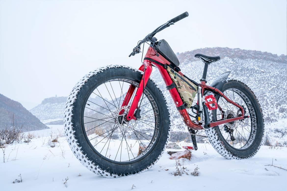 A red fat tire bike stands outdoors in front of a snowy mountain range.