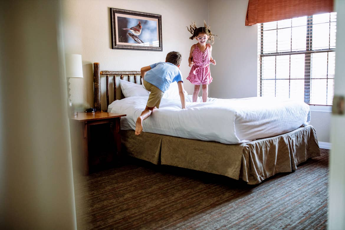 A young boy (left) and young girl (right) jump on the bed in a villa.