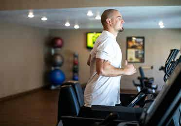 Man running on treadmill in fitness center at Desert Club Resort in Las Vegas, Nevada.