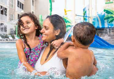 Mother holding two children in outdoor pool at South Beach Resort in Myrtle Beach, South Carolina.
