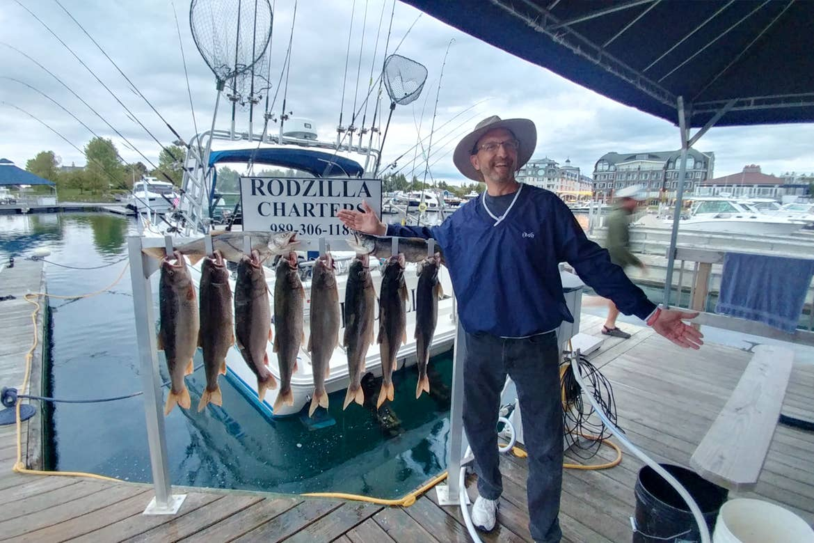 A caucasian man wearing a sun hat, navy windbreaker and jeans stands on a dock near some freshly caught fish with a white sign that reads, 'Rodzilla Charters.'