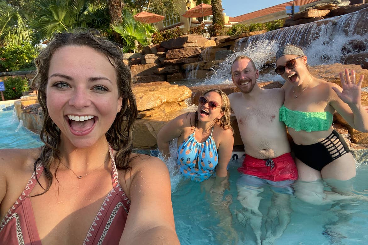Featured Contributor, Angie Orth (left), and her sister and two friends (right) pose next to a water feature at river Island of Orange Lake Resort in Orlando, Florida.