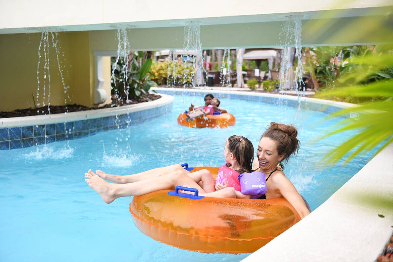Mom and child floating down lazy river on innertube at Orange Lake Resort near Orlando, Florida