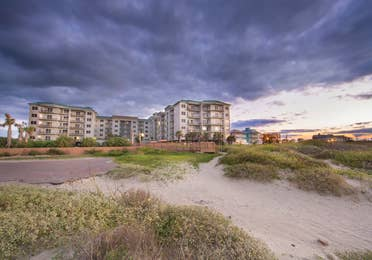 View of Galveston Beach Resort property from the beach at sunset