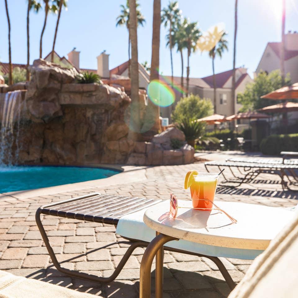 Drink by waterfall pool at Desert Club Resort in Las Vegas, Nevada.