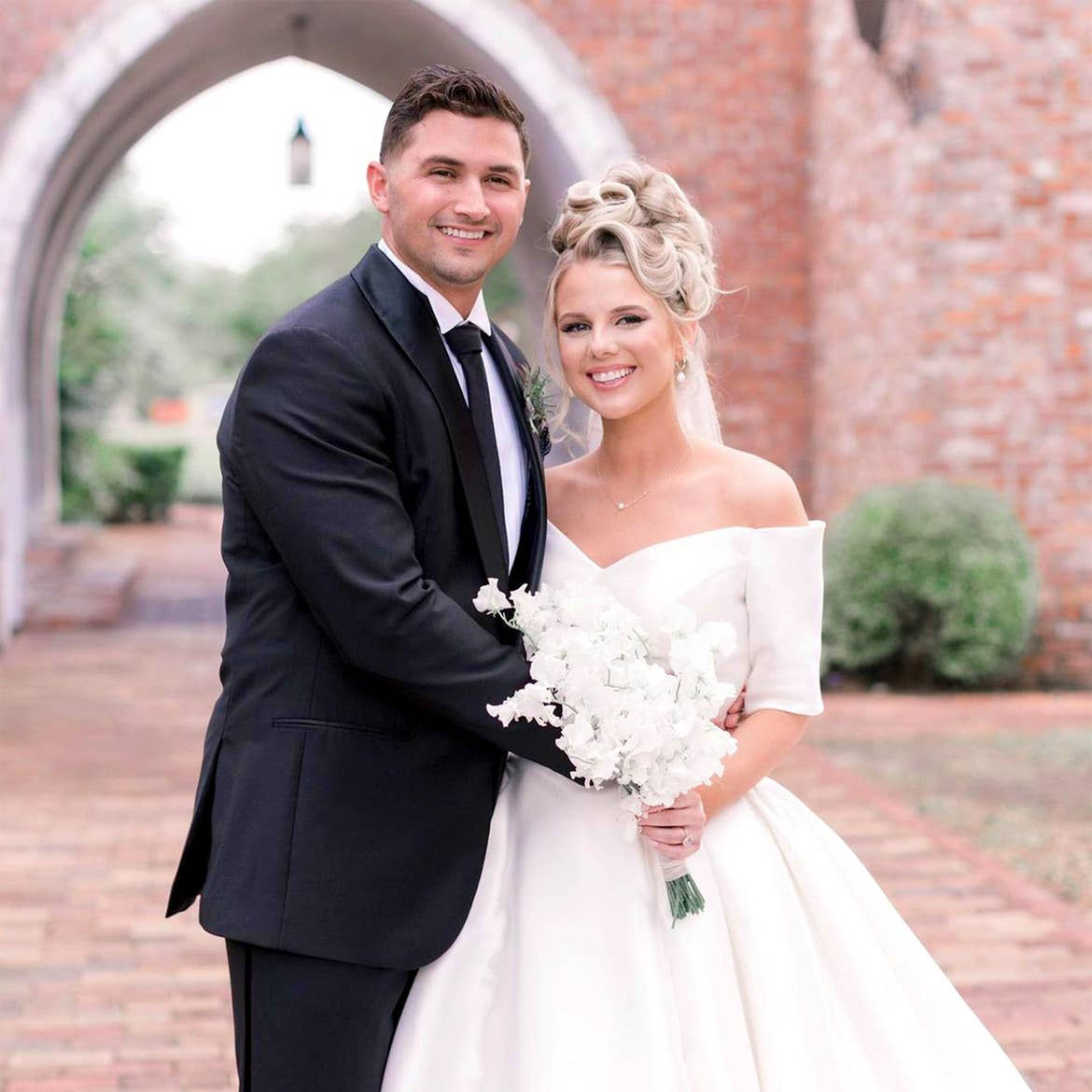 A Latinx groom wearing a black suit and necktie (left) and a caucasian bride with an updo (right) pose next to each other in front of a brick facade.