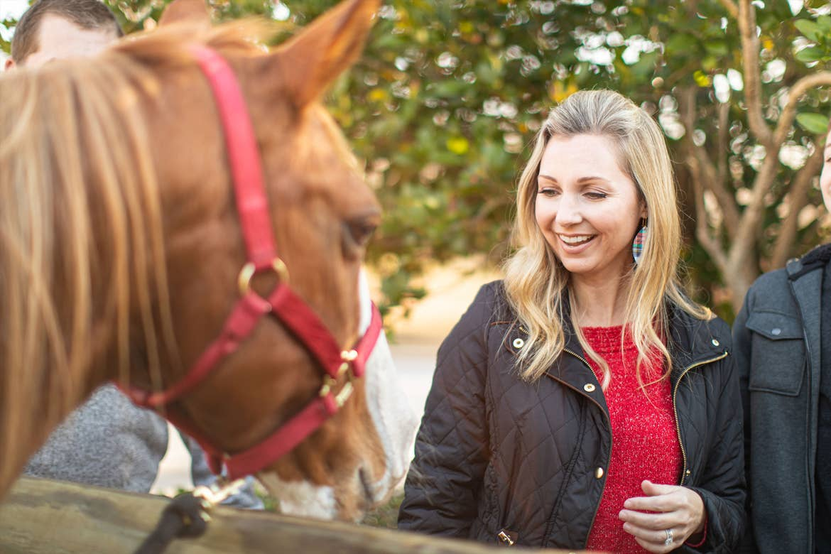Author, Amanda Nall, feeds a horse at our stable in the Villages Resort located in Texas.