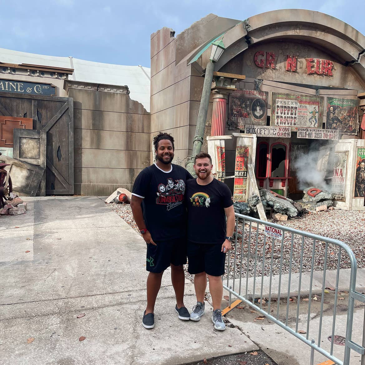 Two men wearing black t-shirts and shorts stand in front of a haunted house.