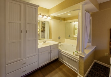 Bathroom with large storage cabinet, vanity, and large soaking tub in a two bedroom villa at Oak n' Spruce Resort in South Lee, Massachusetts