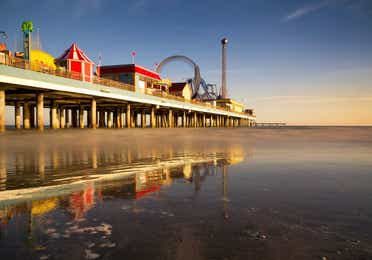 View of the Galveston Pleasure Pier at twilight showing a smooth ocean and carnival rides in motion