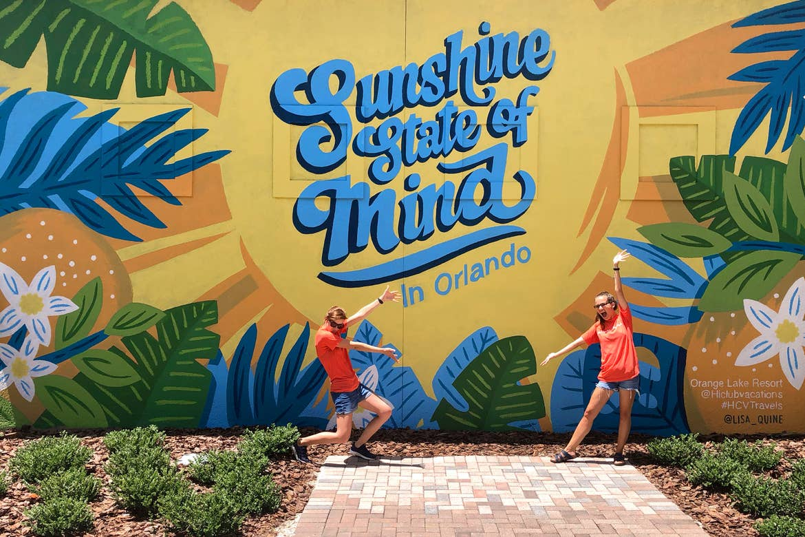 Two caucasian women wearing orange t-shirts and denim shorts stand with their arms extended at our mural located in North Village at Orange Lake Resort in Orlando, Florida.
