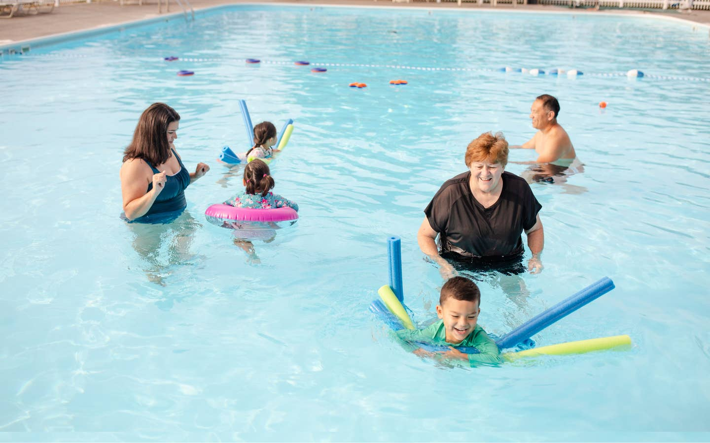 Family swimming in outdoor pool at Holiday Hills Resort in Branson, Missouri.